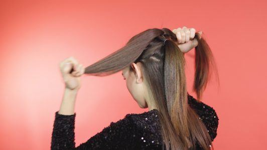 Pull through braid brunette girl separating ponytail with hands