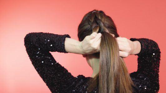 Pull through braid brunette girl tying hair into a braid