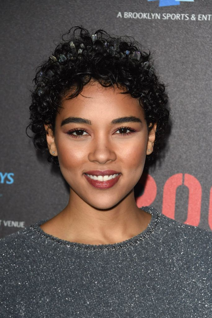 close up shot of alexandra shipp with curly black pixie cut hairstyle, wearing a tiara crown on the red carpet