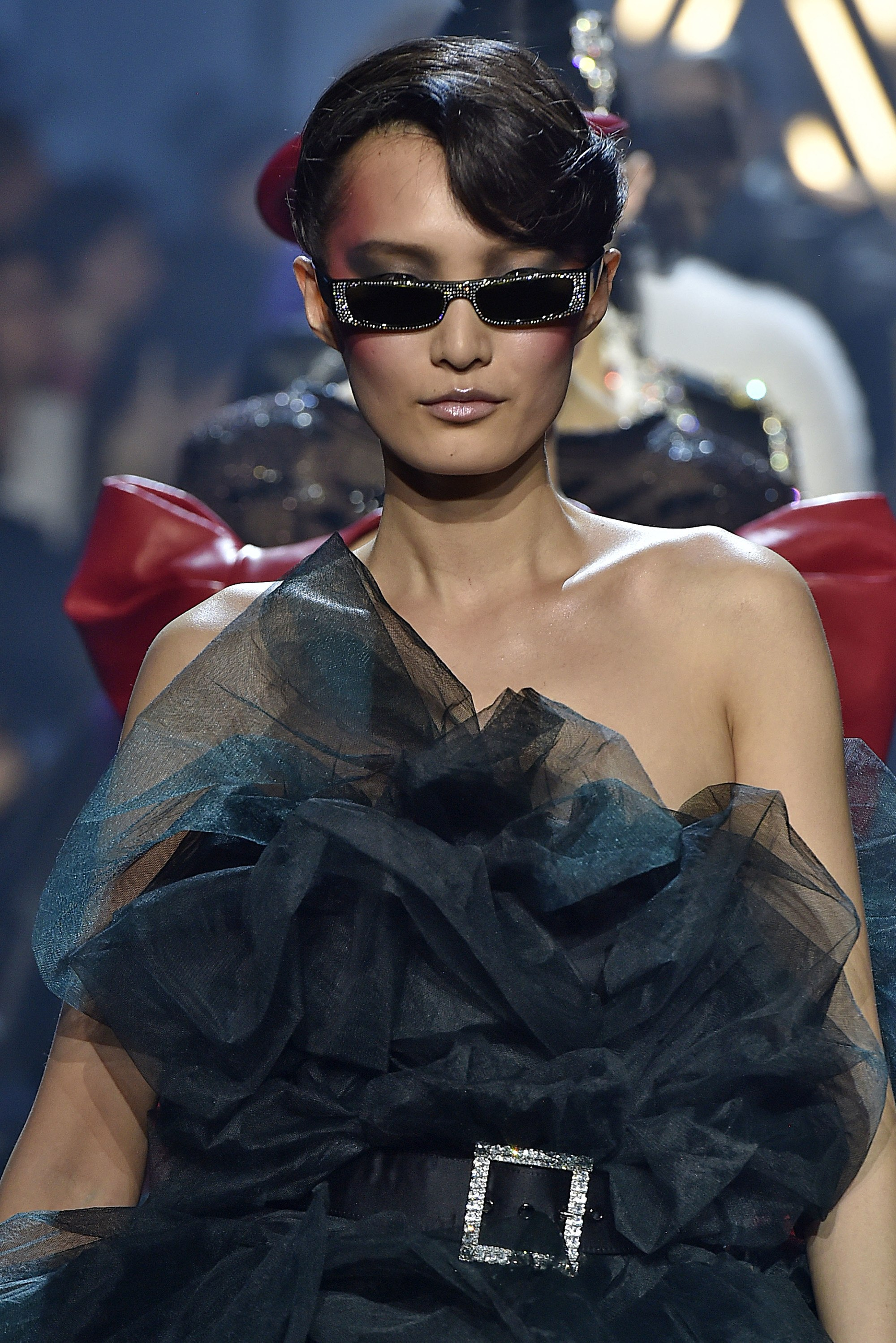 model with brown hair in elegant updo wearing small sunglasses on runway
