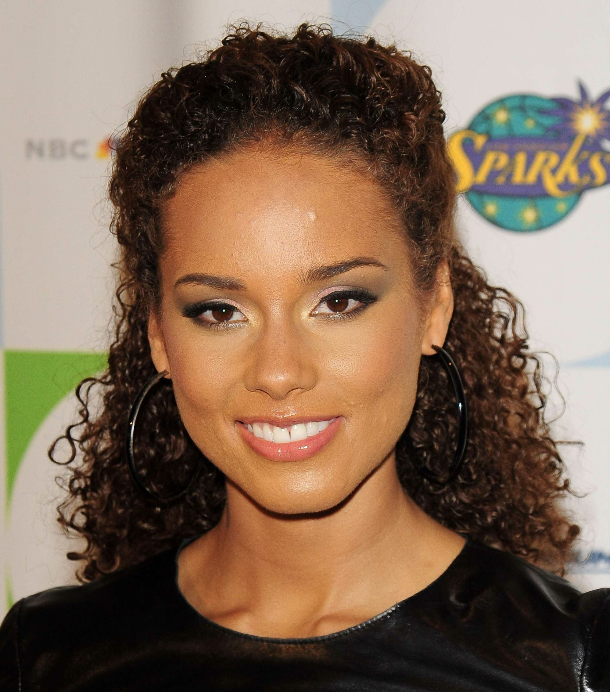 alicia keys in 2010 with a curly half up half down hairstyle