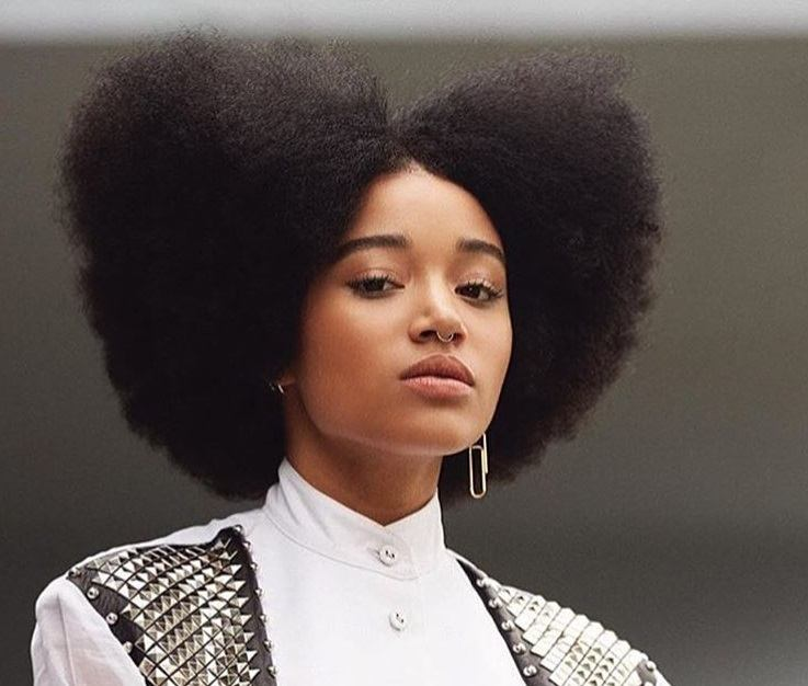 close up shot of amandlas stenberg with trapezoid afro hairstyle, wearing smart top and posing outside