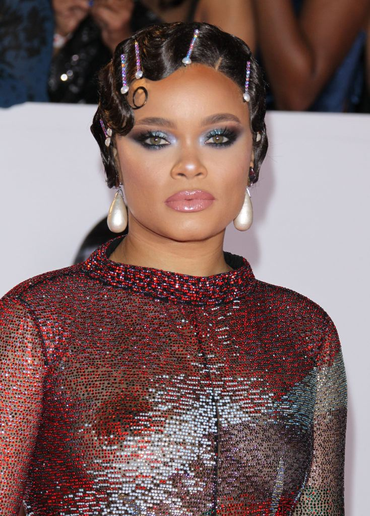 close up shot on andra day with pearly bobby pins in her 1920s inspired hairstyle, wearing purple dress and posing on the naacp image awards red carpet