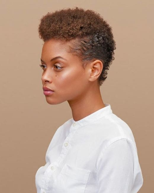 2019 haircut predictions: Woman with golden brown naturally curly short hair styled with a mohawk.