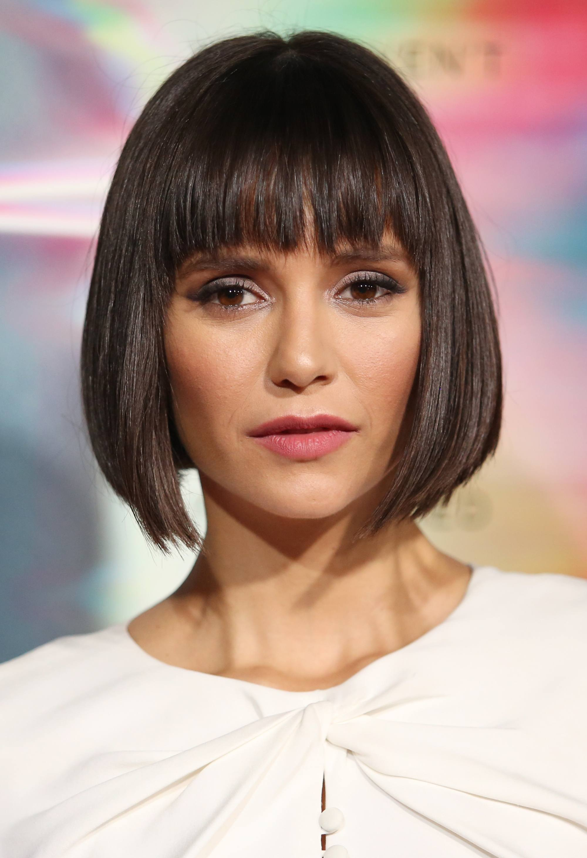 close up shot of anna dovrec with chanel haircut hairstyle, with a-line cut and a white top, posing on the red carpet