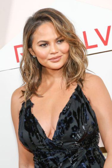 curly haircuts for round faces: close up shot of chrissy teigen with beachy curls, wearing black dress and posing on the red carpet