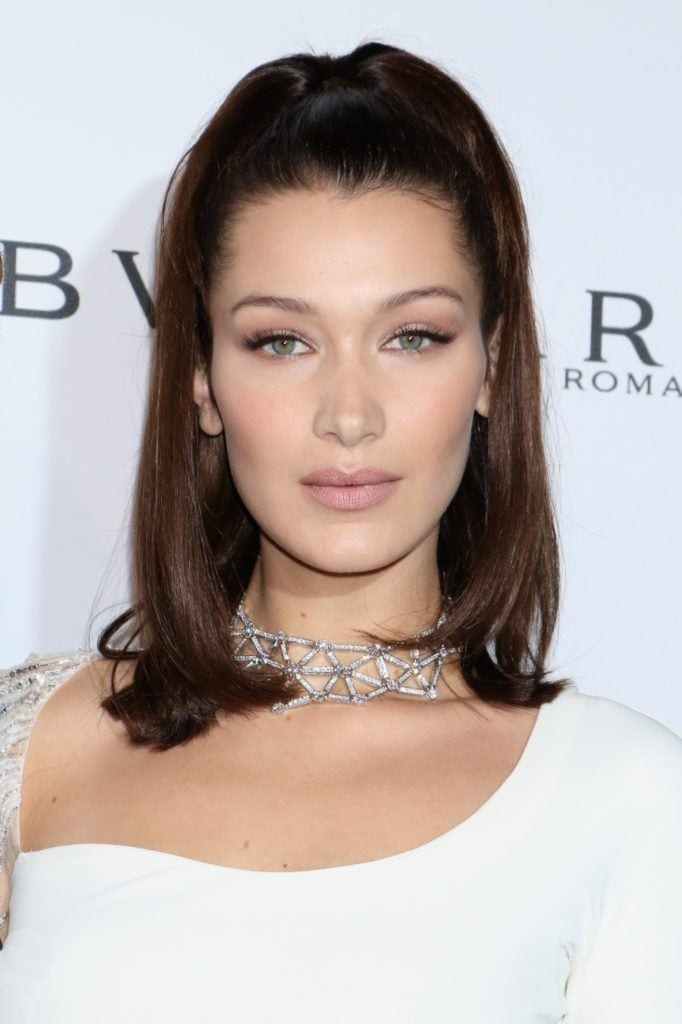 short to mid length hairstyles: close up shot of bella hadid with half up half down ponyail hairstyle on the red carpet