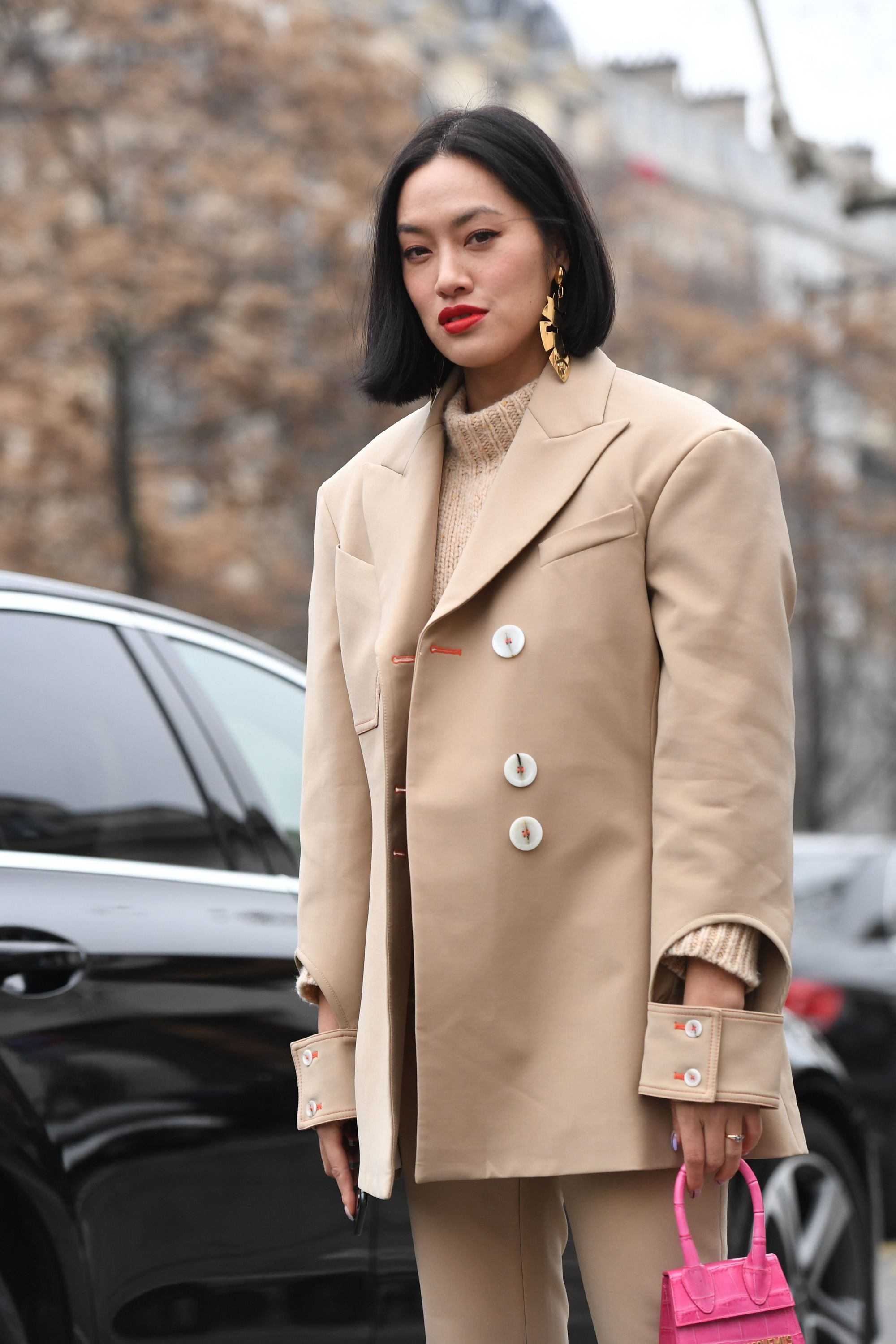 Hair trends 2019: Street style of woman with straight dark brown jawline bob wearing a beige jacket.