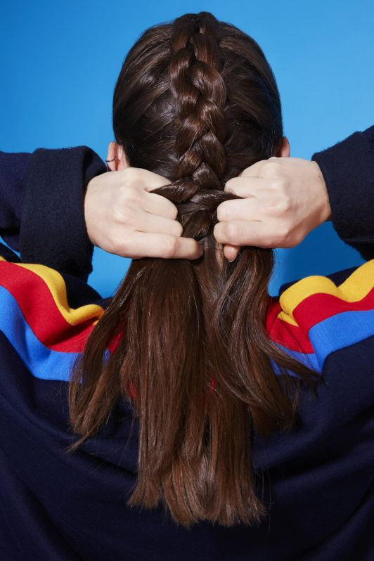 How to dutch braid: Back view of a brunette girl plaiting her hair into a Dutch braid, wearing a jumper with rainbow stripes and standing against a blue background