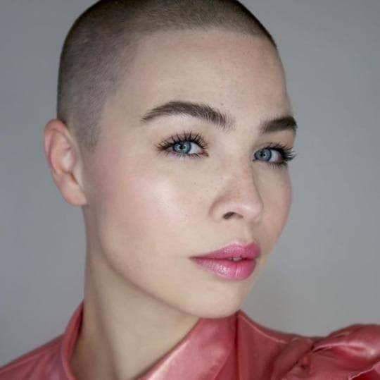woman with a dark buzz cut haircut and pink lipgloss