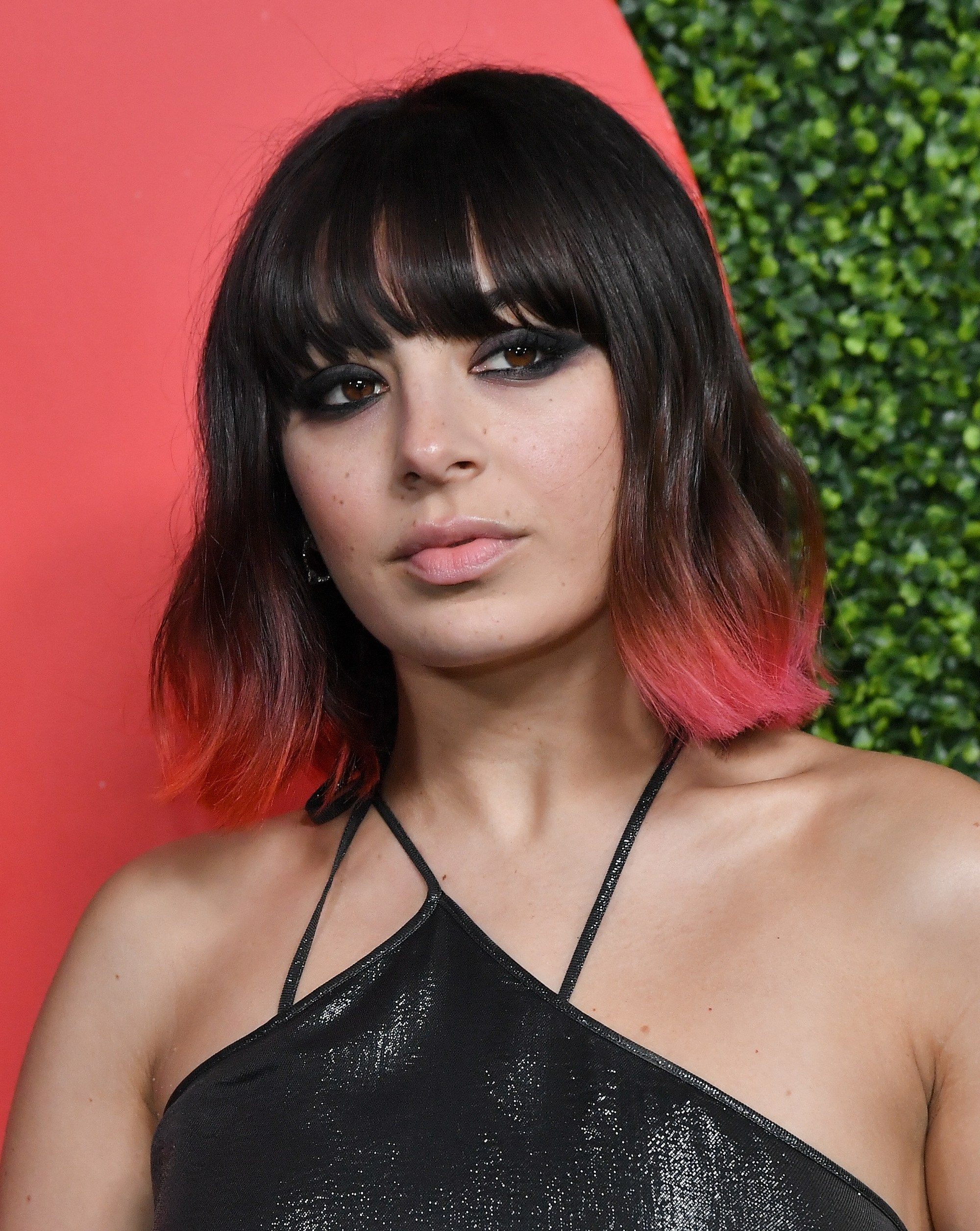 Charlie XCX with wavy bob haircut with neon pink ombre on the ends, with feathered fringe on the red carpet