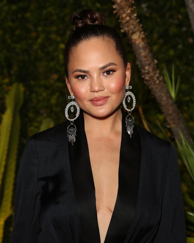 updo hairstyles for work: close up shot of chrissy teigen with braided top knot hairstyle on the red carpet, wearing all black