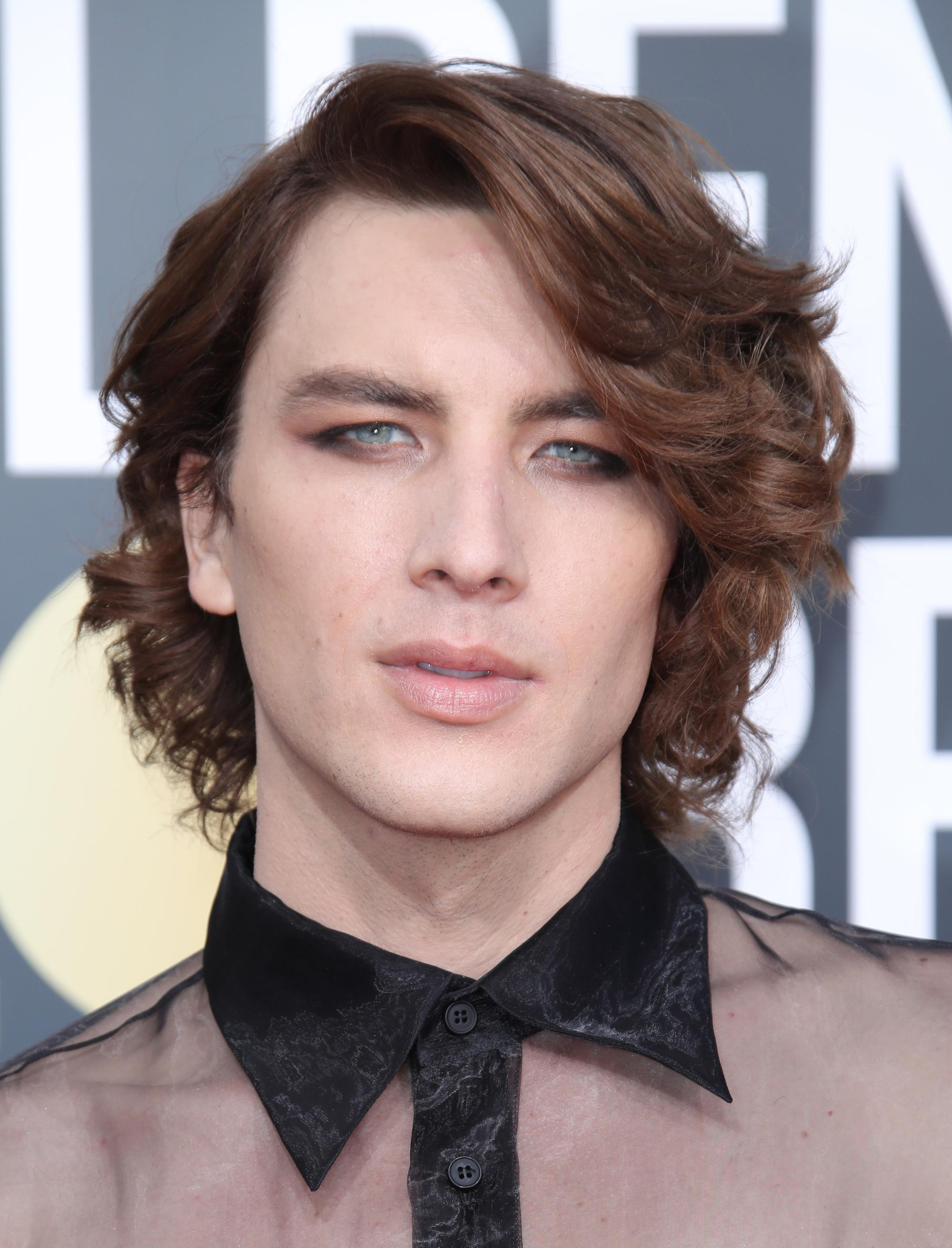 Golden Globes 2019: Close-up of actor Cody Fern with wavy brown swooped mid-length hair, wearing a sheer black shirt with smoky eye makeup