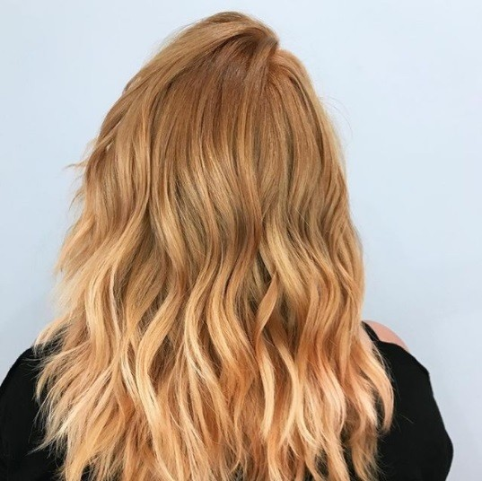 back view of a woman with copper blonde ombre shoulder length wavy hair