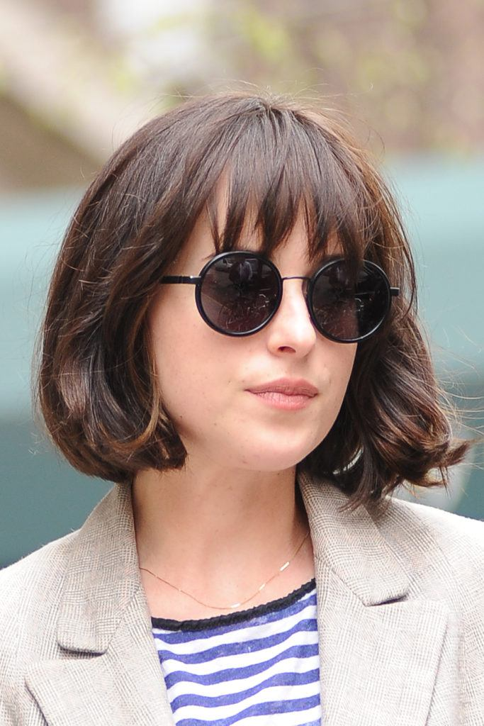 Close up shot of Dakota Johnson with a messy French girl haircut with wispy bangs,