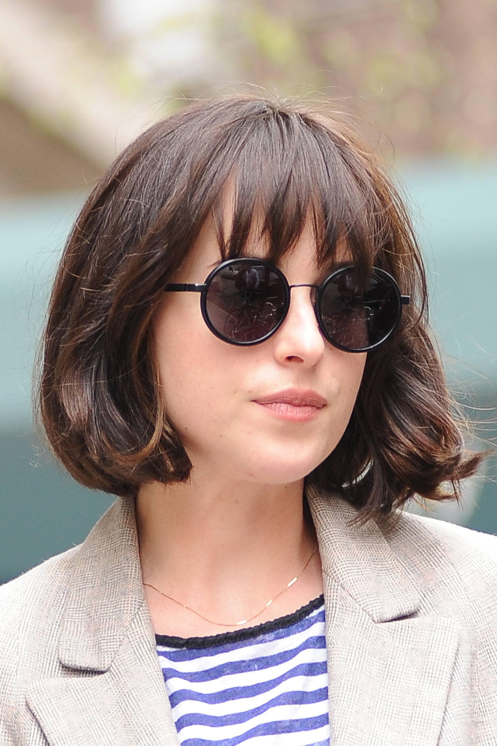 Close up shot of Dakota Johnson with a messy French girl haircut with wispy bangs, wearing circle sunglasses with a white trench coat