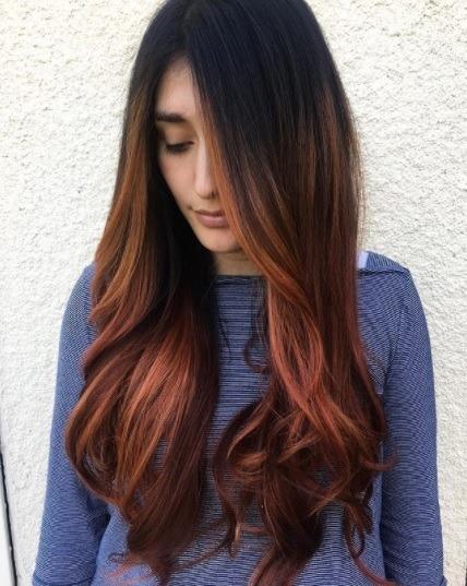 woman with long dark hair with brunette roots and copper ombre tips