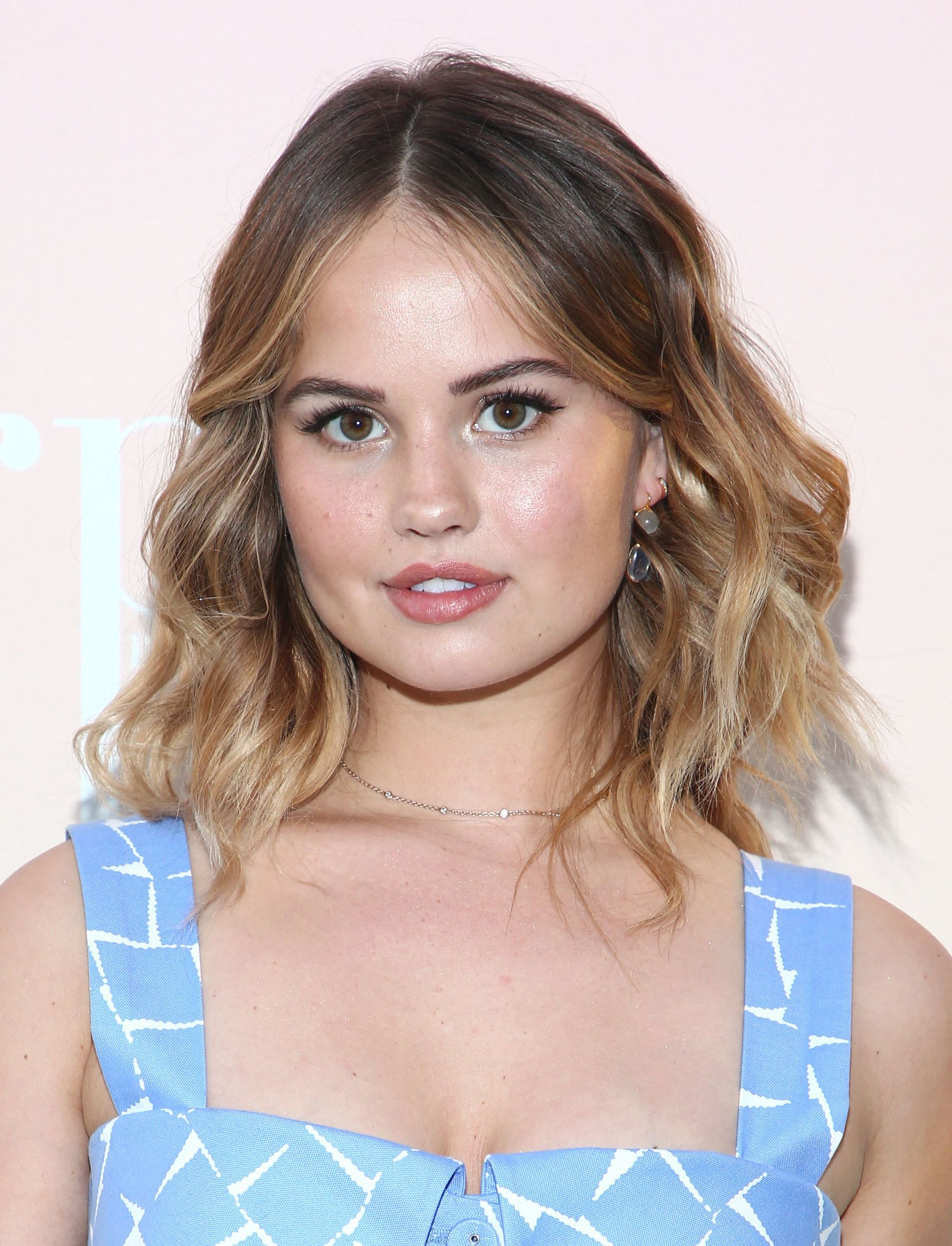 short to medium hairstyles: close up shot of debby ryan with wavy medium hairstyle, wearing blue and posing on red carpet