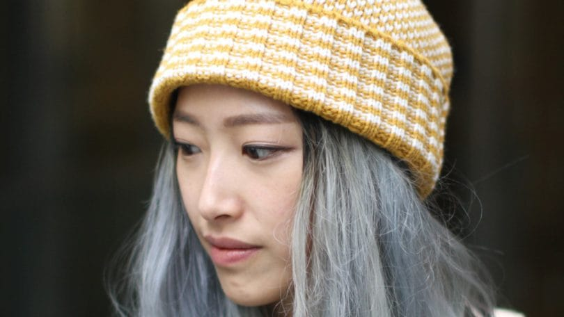 Best deep conditioner for damaged hair: Woman with grey long hair under wolly hat street style.
