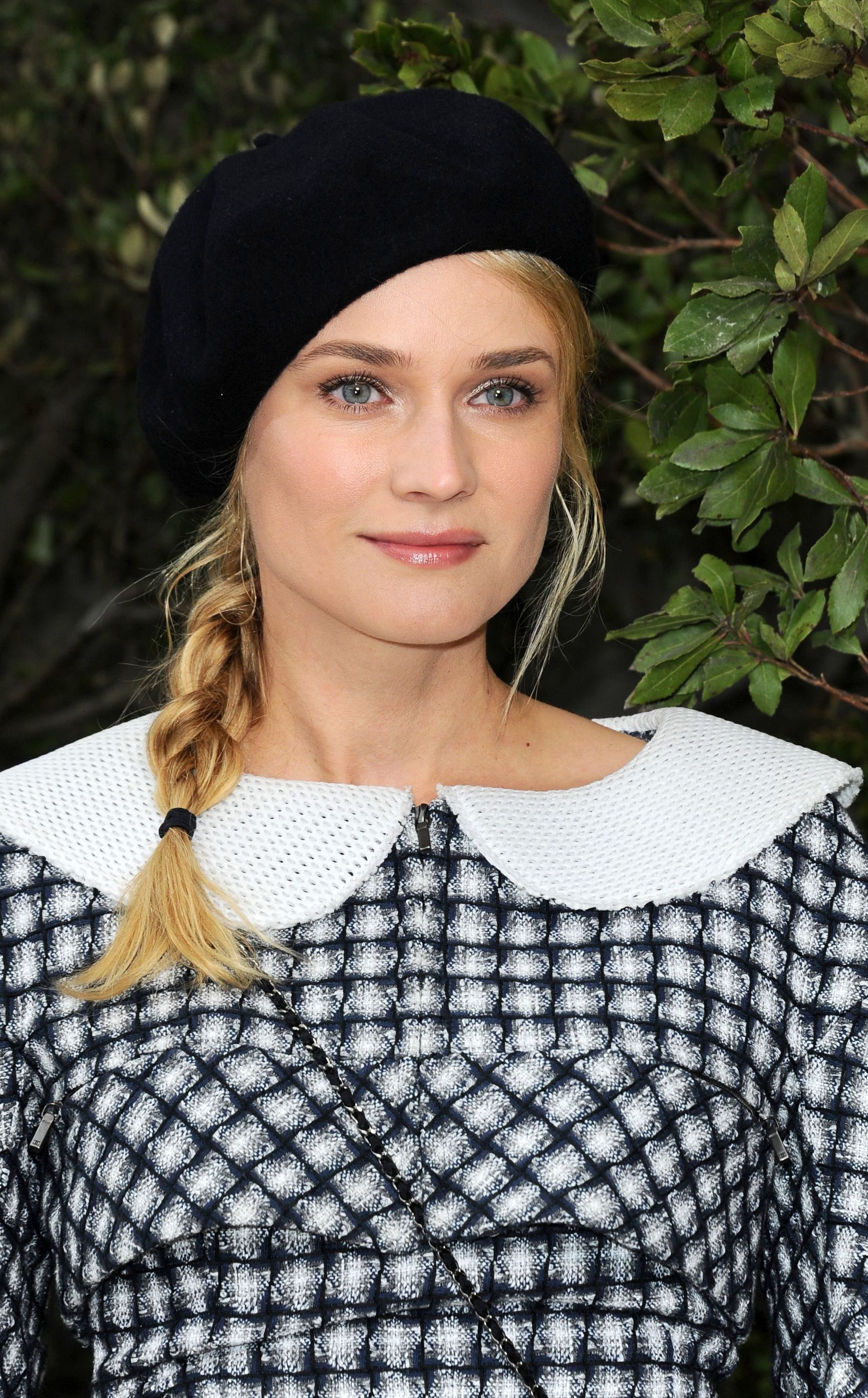 medium short hairstyle: close up shot of diane kruger with side braided hairstyle, wearing beret and gingham dress