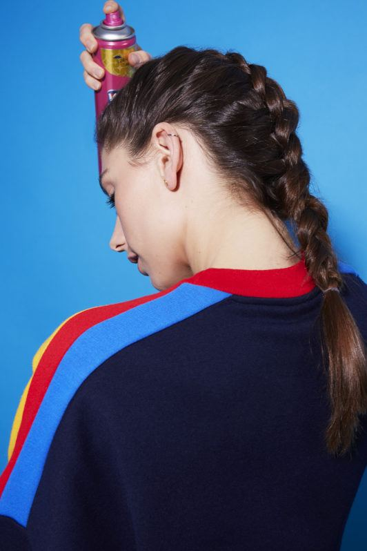 How to dutch braid: Back view of a brunette girl with a Dutch braid hairstyle spraying her hair with hairspray