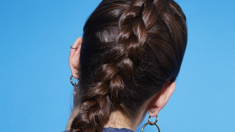 How to dutch braid: Back view of a brunette with her hair in a Dutch braid, against a blue background