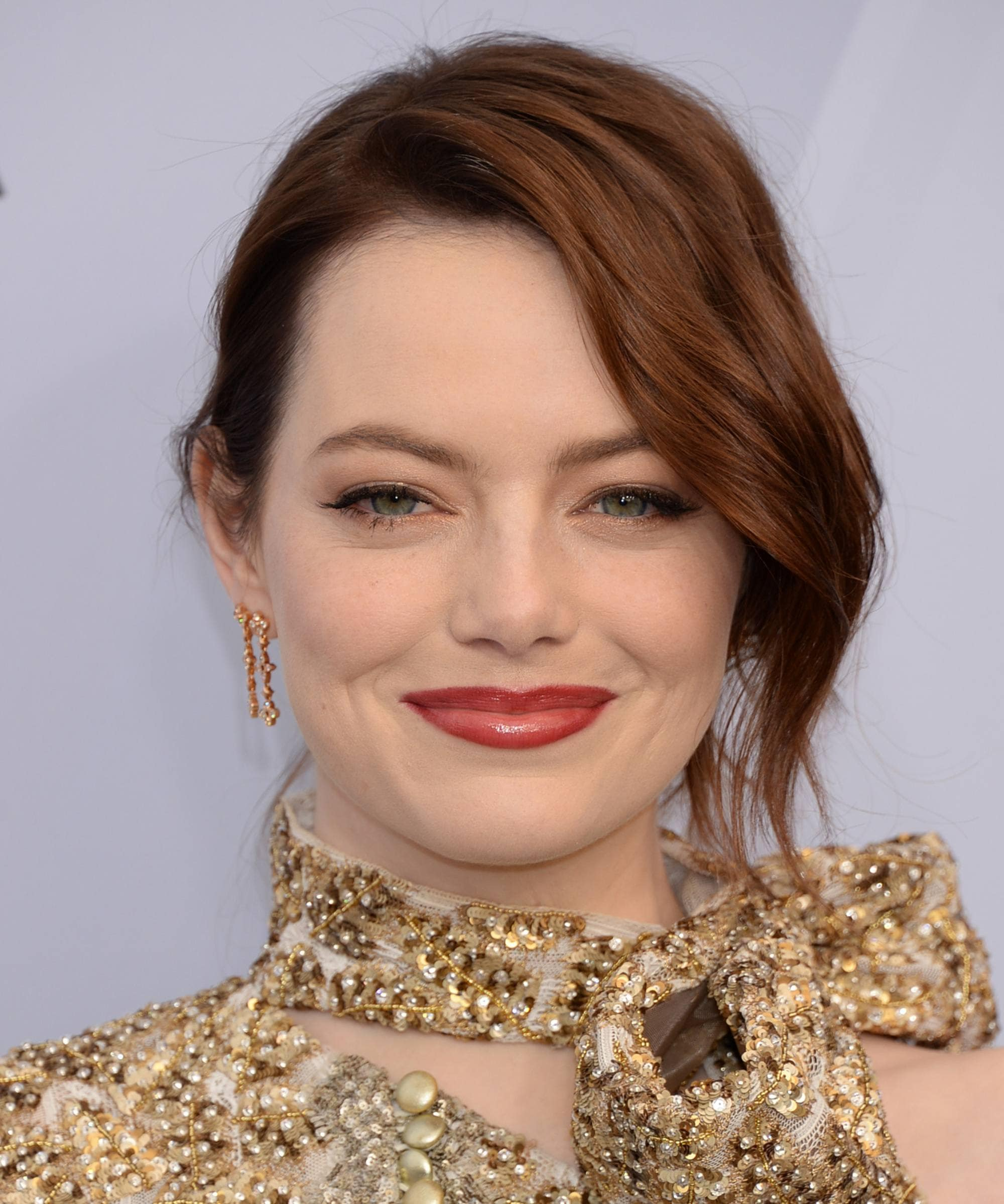 Famous redheads: Emma Stone with dark red wavy hair styled in a updo with a loose long side fringe wearing a gold high neck dress.