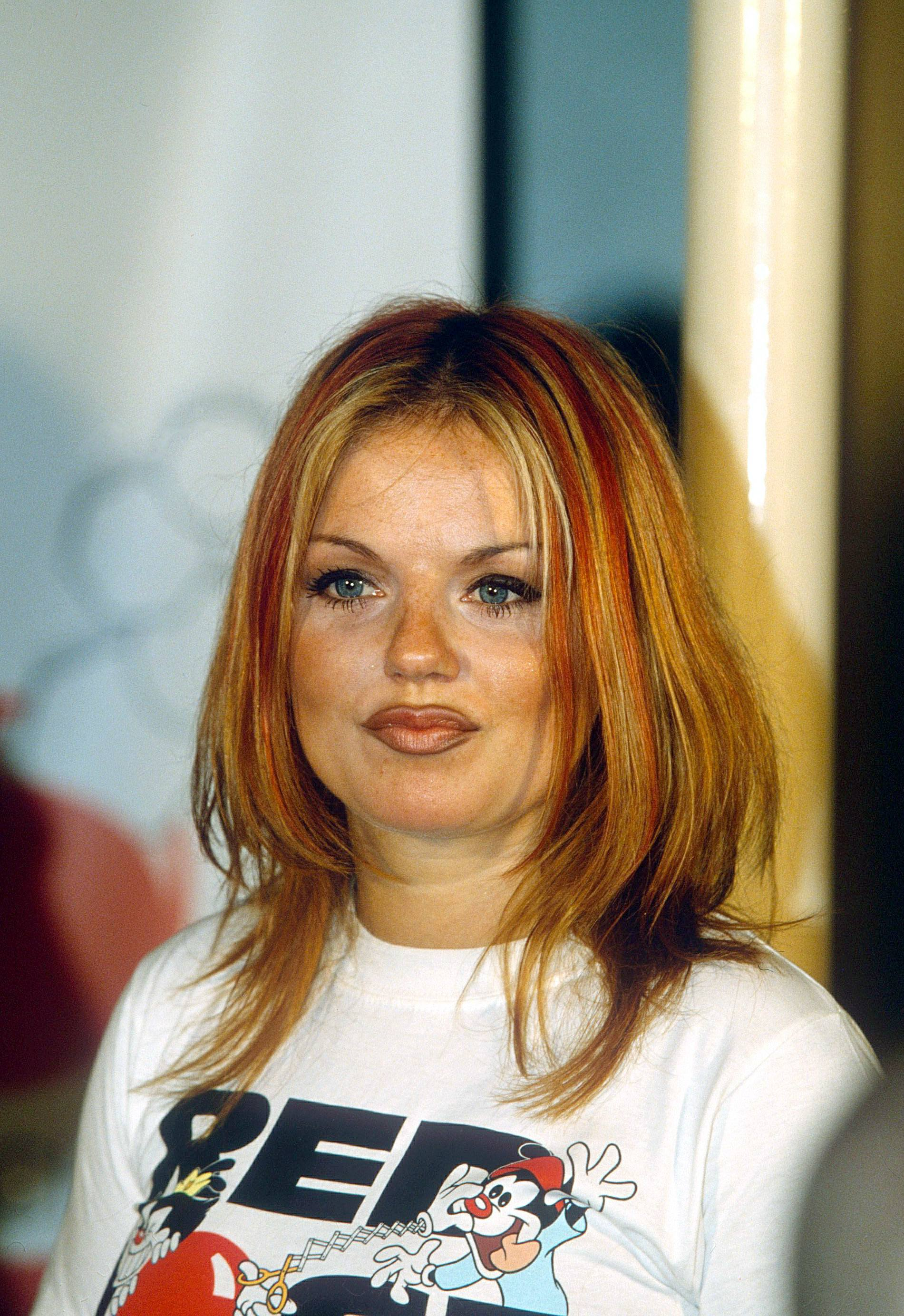 Famous redheads: Geri Halliwell with straight medium length giner hair with blonde highlights wearing a white t-shirt.