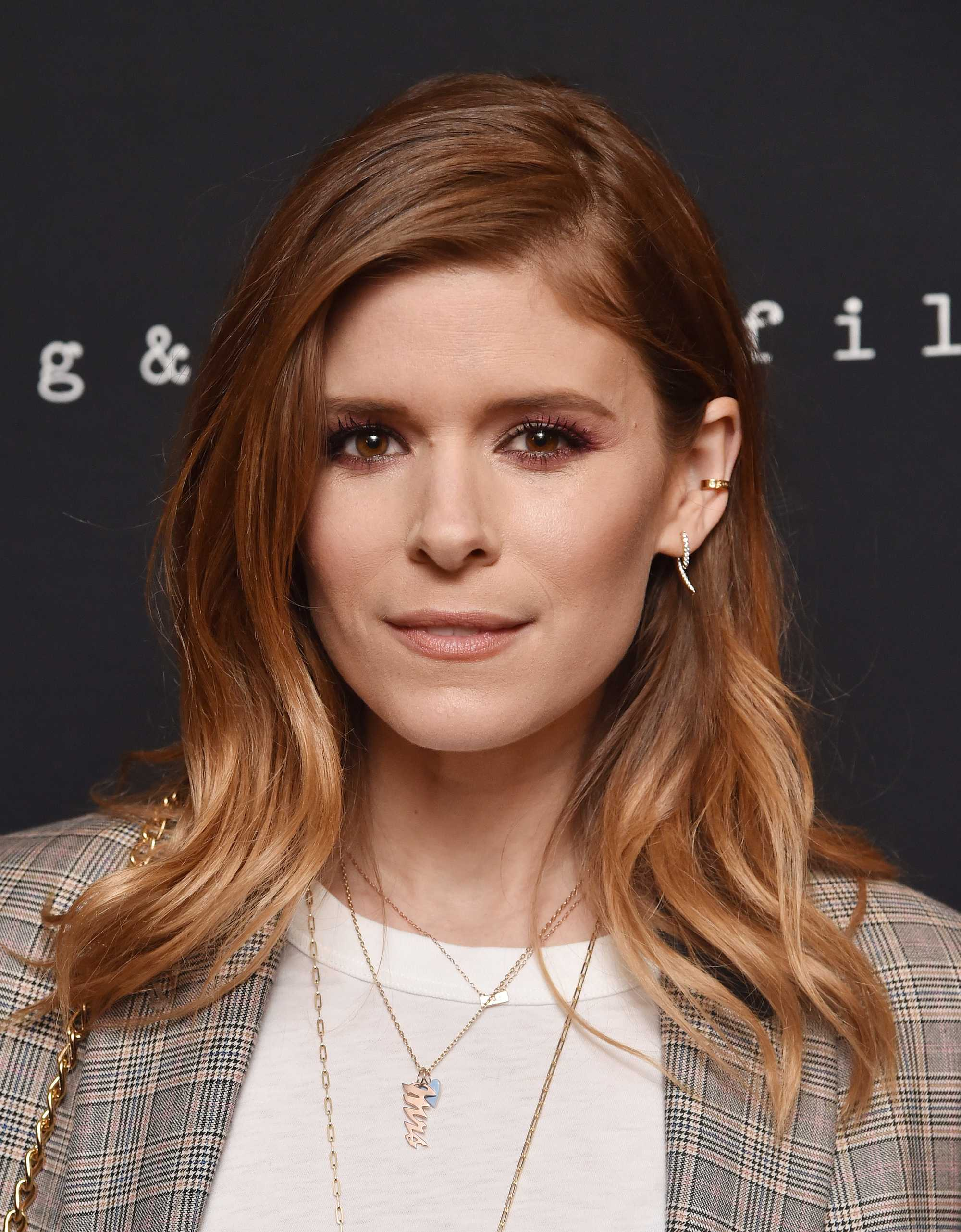Famous redheads: Kate Mara with medium length wavy auburn red brown balayage wearing a white t shirt and grey checked blazer.