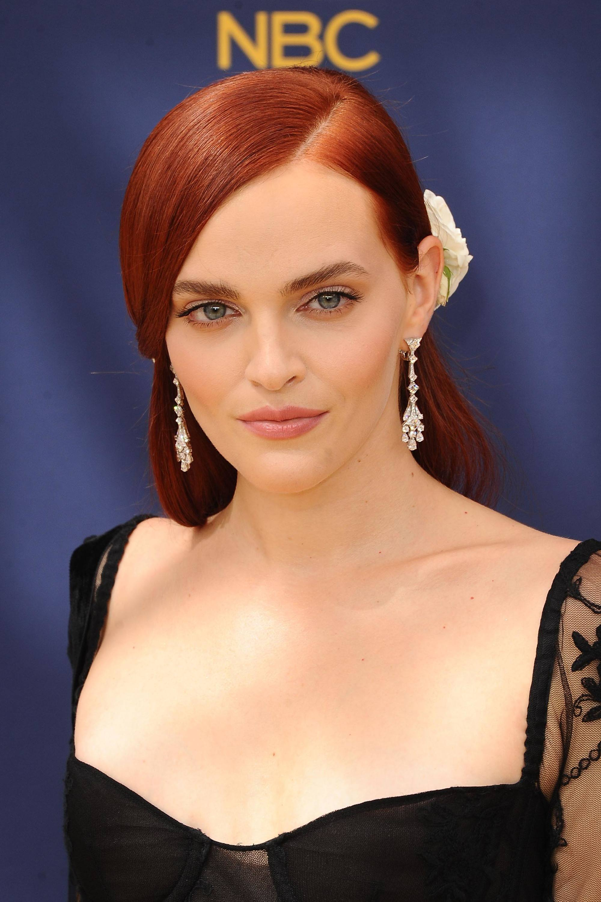 Famous redheads: Madeline Brewer with long straight dark red hair styled in a side parting with a large white flower accessory wearing a black lace dress.