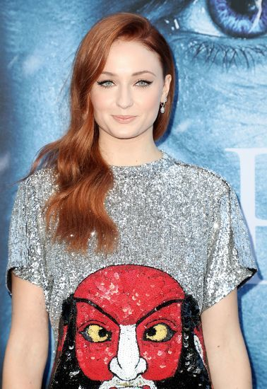 Famous redheads: Sophie Turner with long wavy red hair wearing a sparkly tshirt dress.