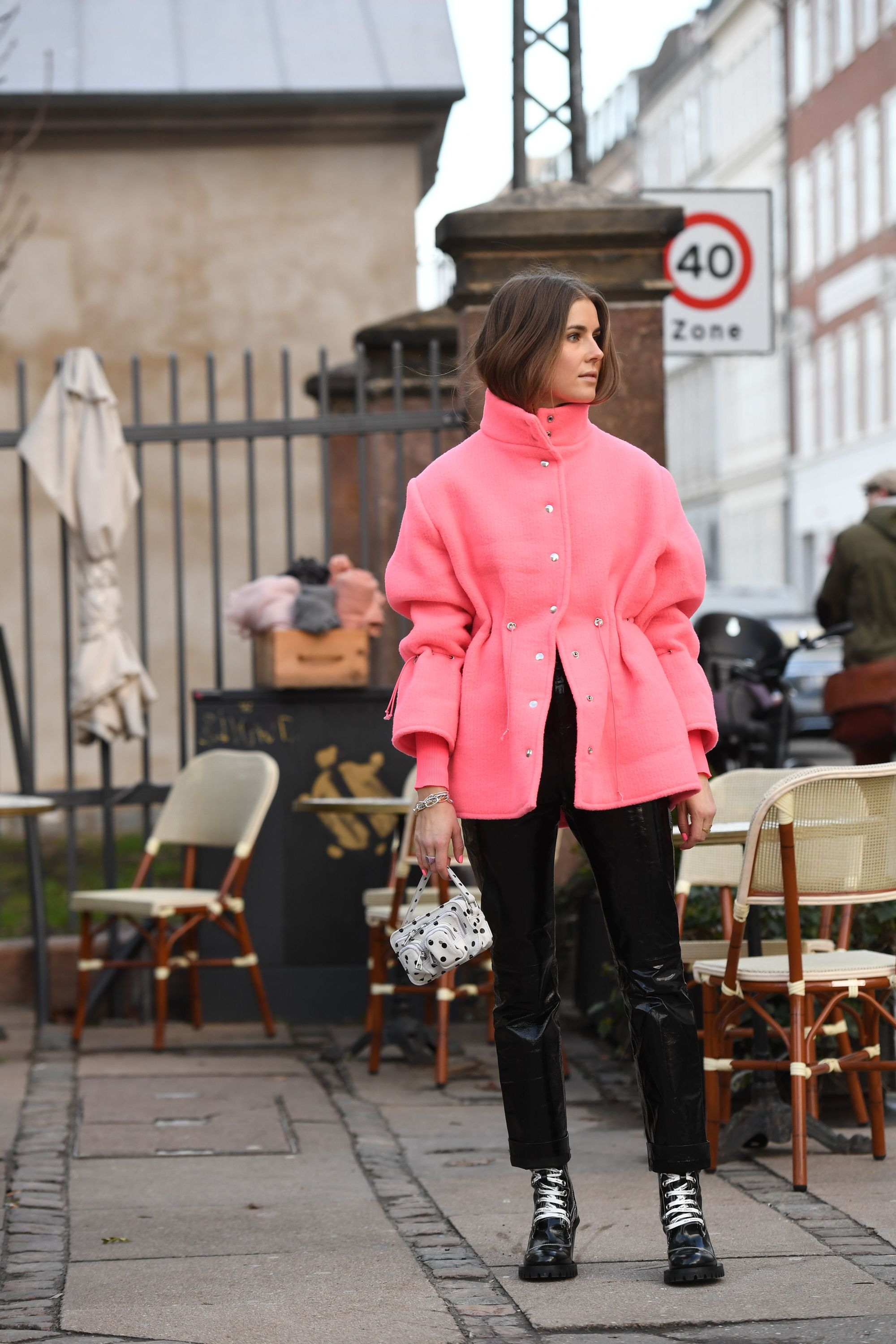 Hair trends 2019: Street style woman with brown hair tucked into her pink jacket.