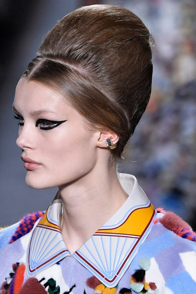 Paris Haute Couture Week fw18: close up shot of a woman with medium brown hair styled into a beehive updo, wearing cat eye liner and a printed top, on the fendi runway