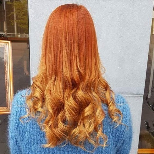 back view of a woman with orange copper ombre long curly hair
