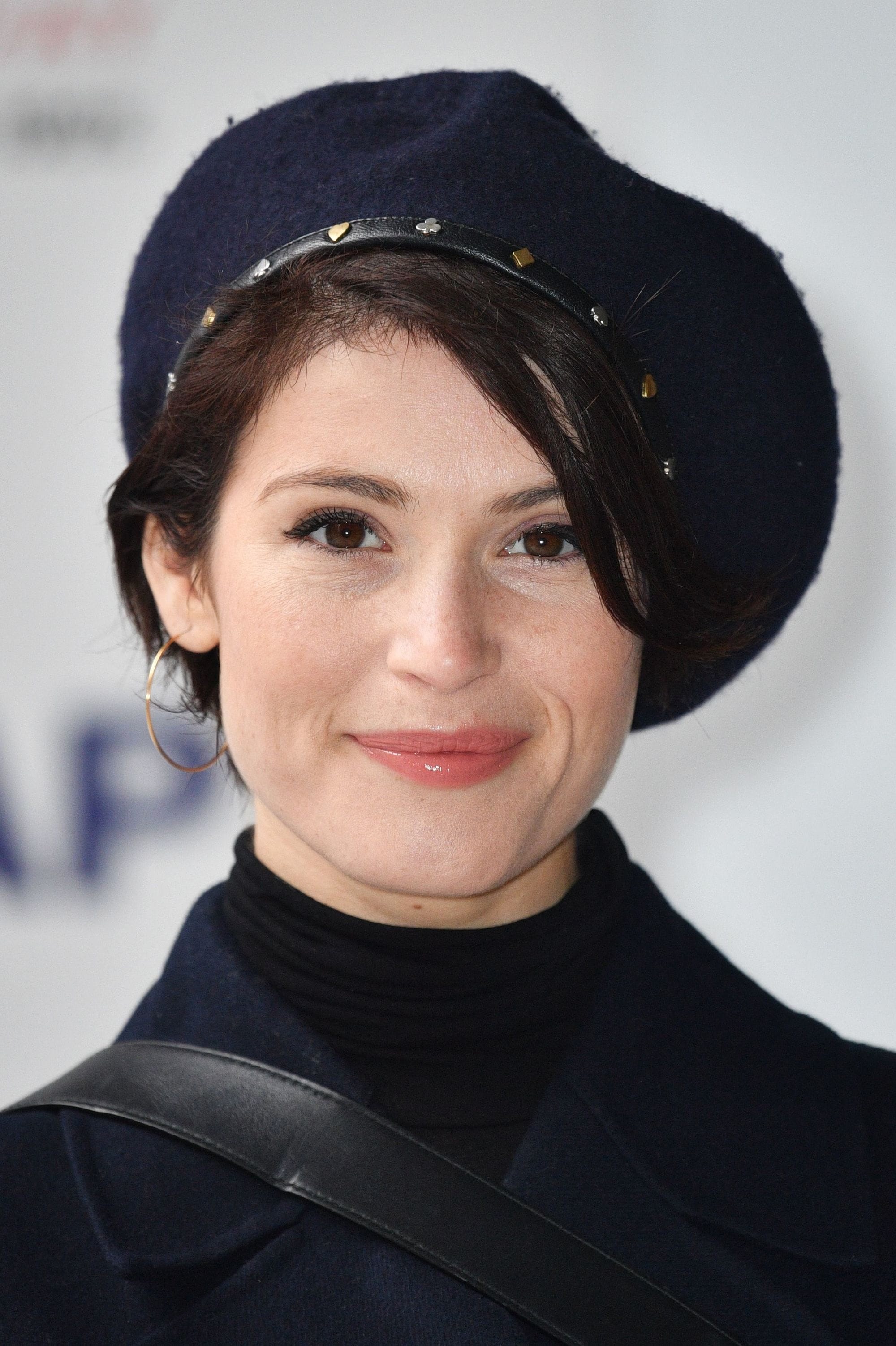 close up shot of gemma arterton with sleek pixie and beret hairstyle, posing and wearing all black on the red carpet