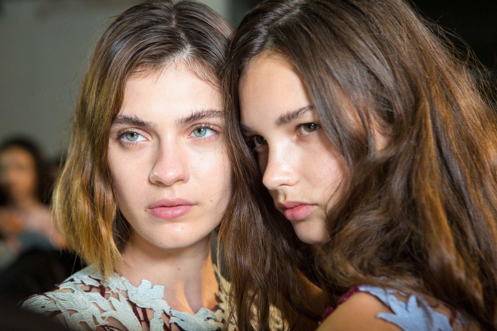 two models backstage at a fashion show, one with short light brown hair cut into a wavy bob and the other with long brunette hair styled into waves