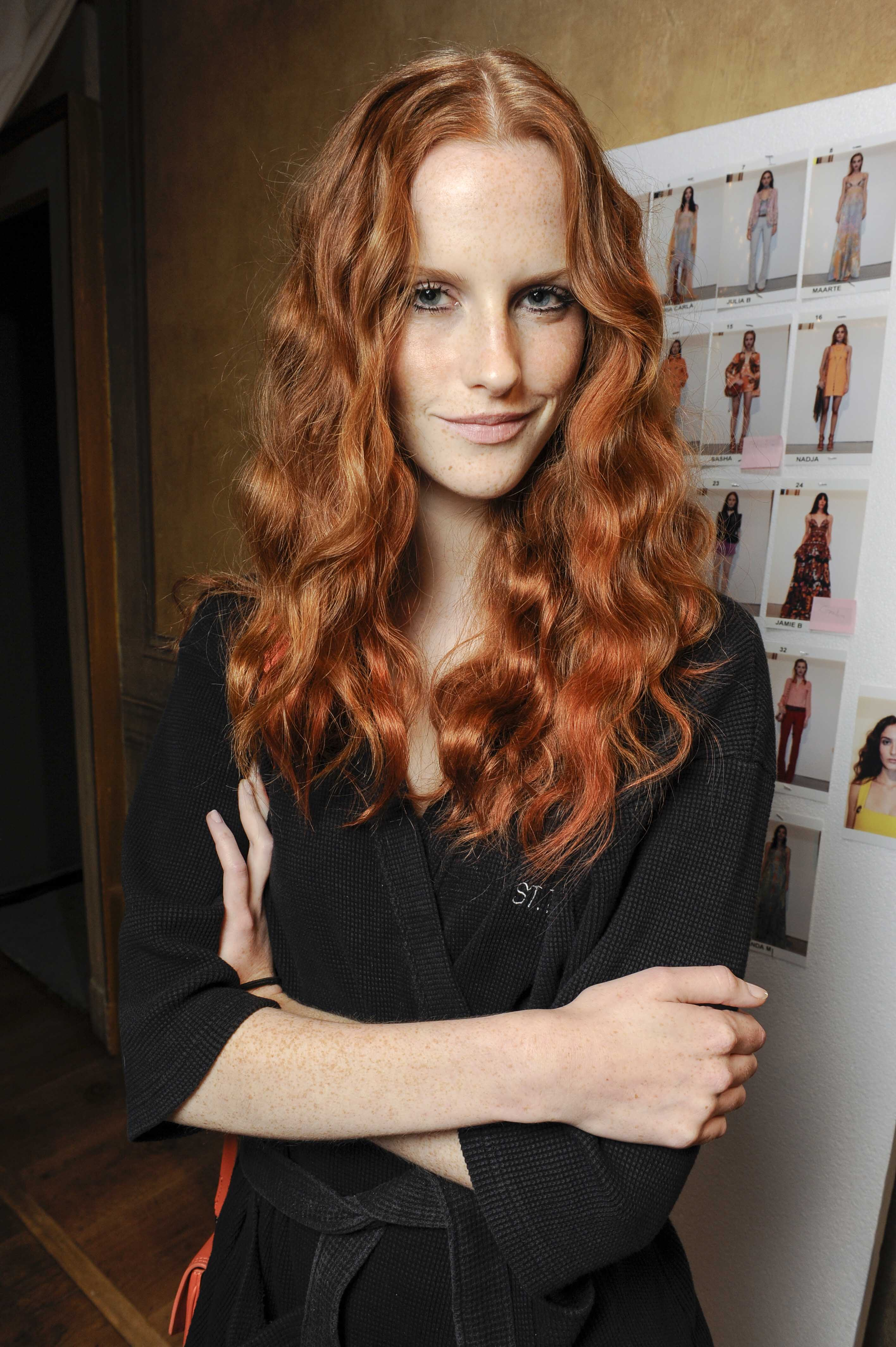 Wavy hair tips Girl with copper curly hair standing backstage with folded arms