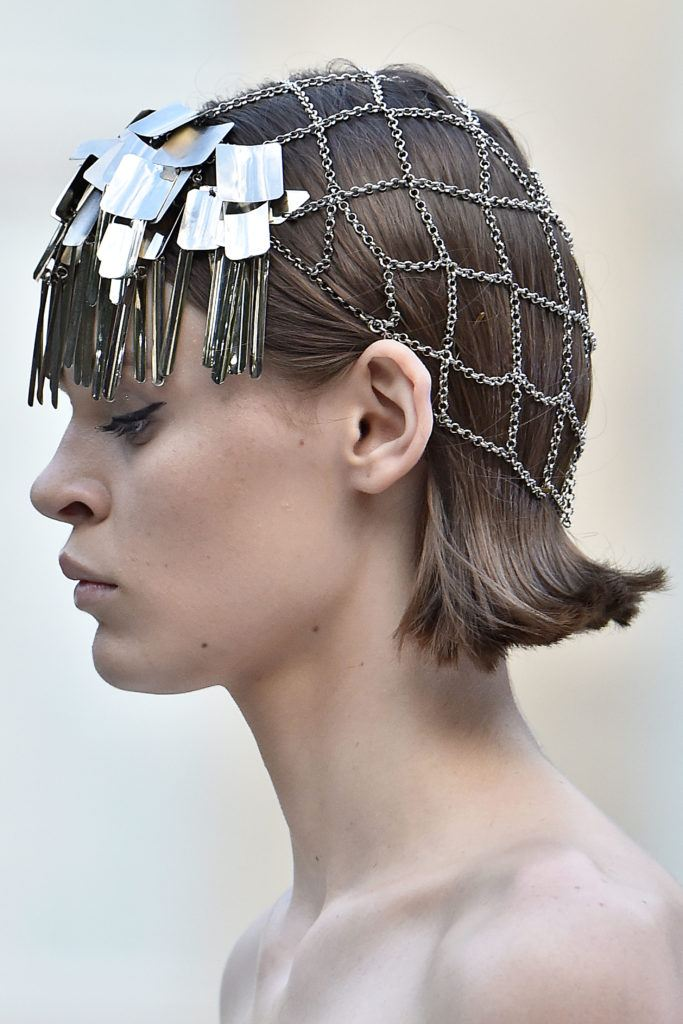 Paris Haute Couture Week fw18: close up shot of a model with flipped light brown bob, wearing hair accessories over it, backstage at the Givenchy haute couture week
