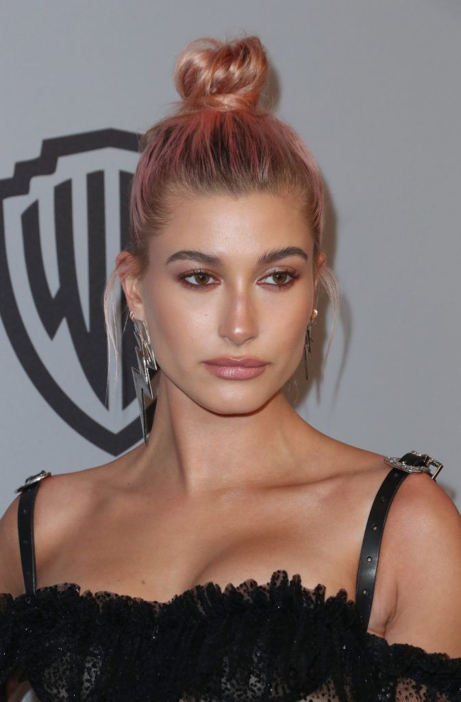 model hailey baldwin with her pink hair in a top knot with dark grown out roots