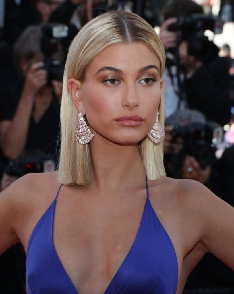 straight short hairstyle: close up shot of hailey baldwin with straight, sleek hair, wearing blue top and posing on the red carpet