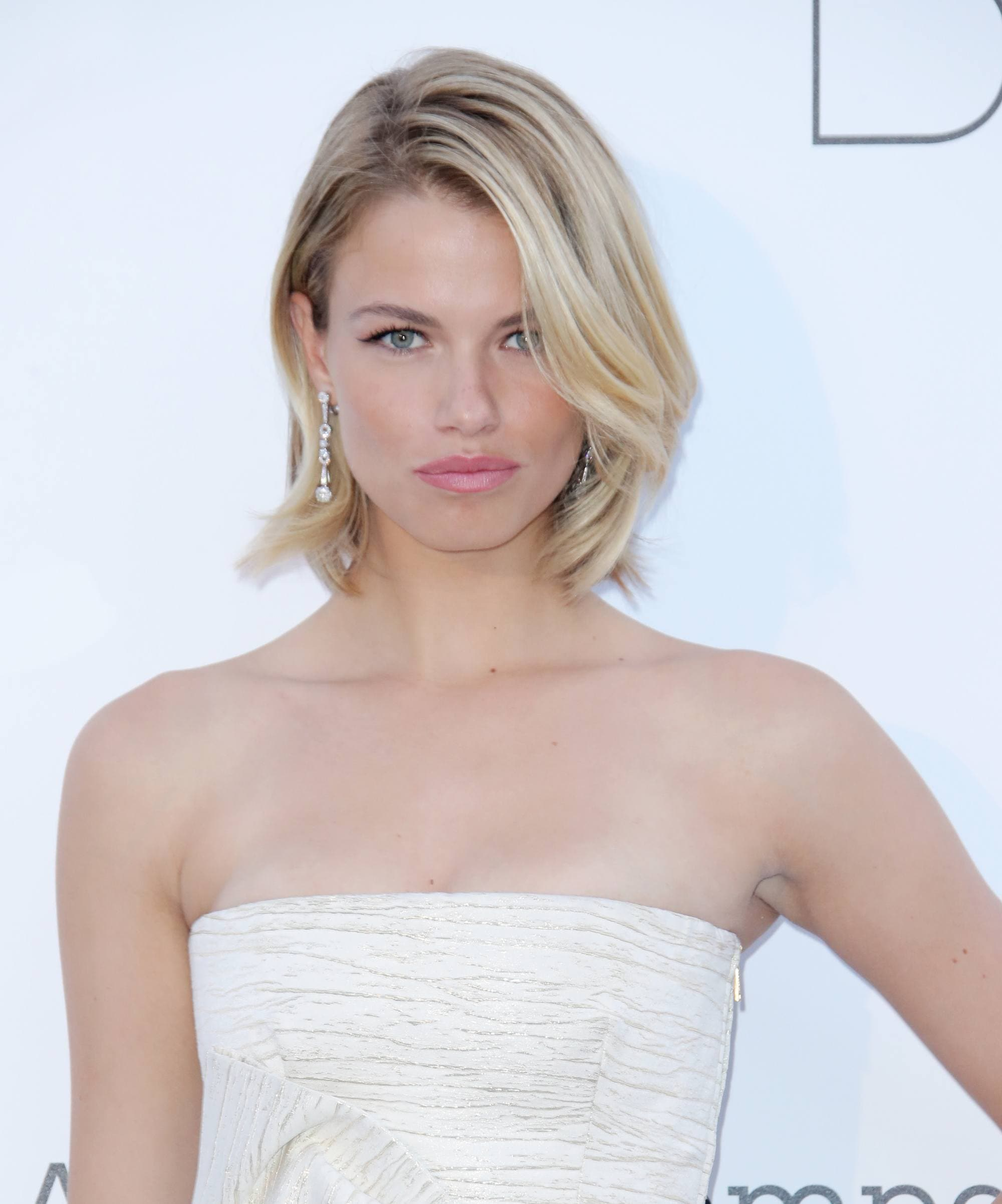 Hailey Clauson with short blonde bob haircut styled into loose waves on the red carpet