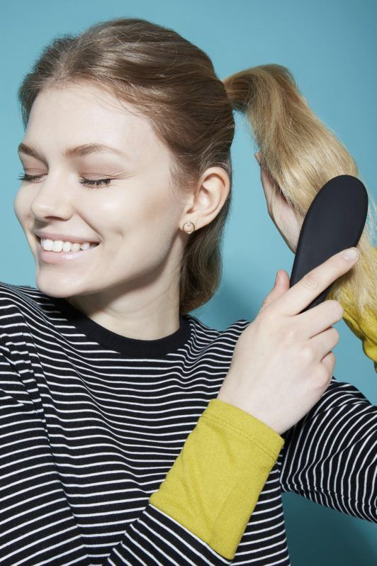 Bow hairstyle Hair bow tutorial blonde girl brushing ponytail and smiling