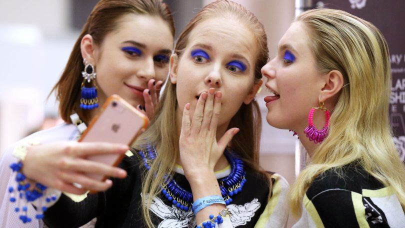 close up shot of three models backstage, posing and holding an iphone