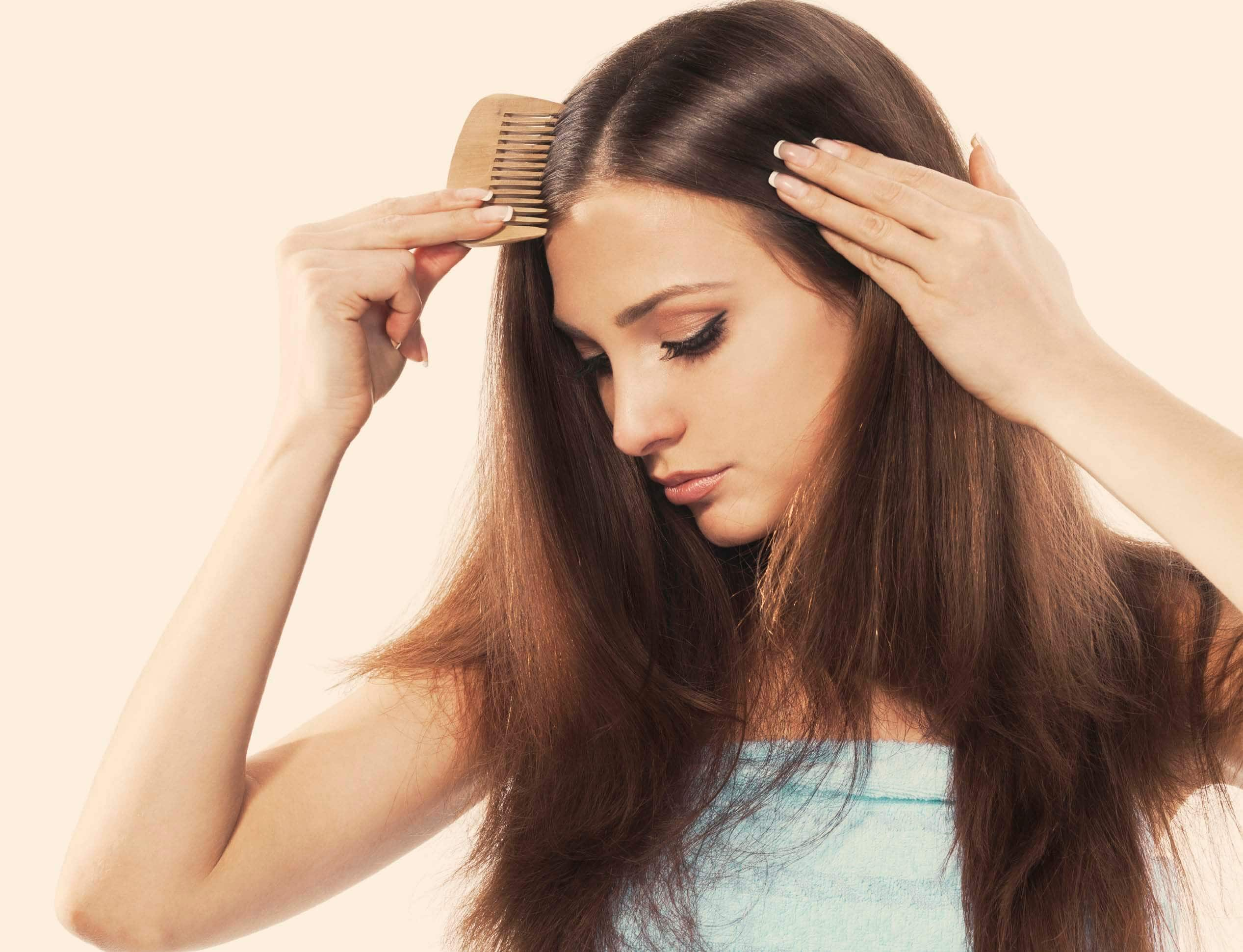Hair loss: Brunette woman combing her hair and looking down