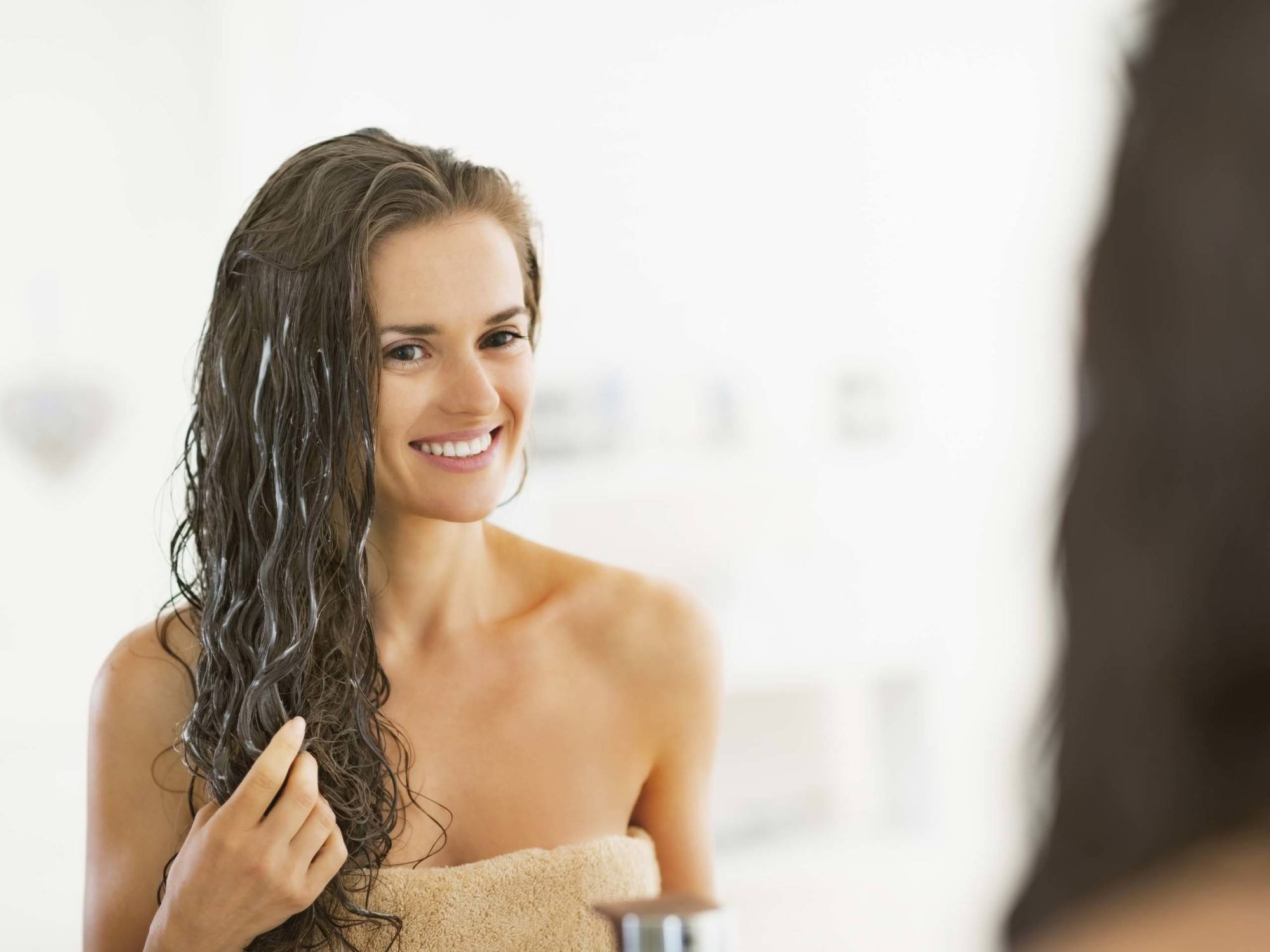Washing hair after colouring girl smiling in the mirror with hair mask