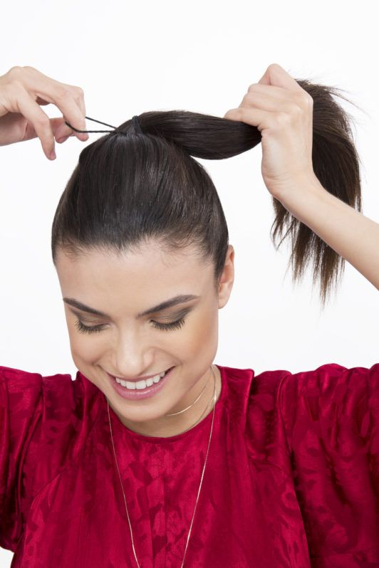 How to create sock curls brunette girl tying hair into a ponytail