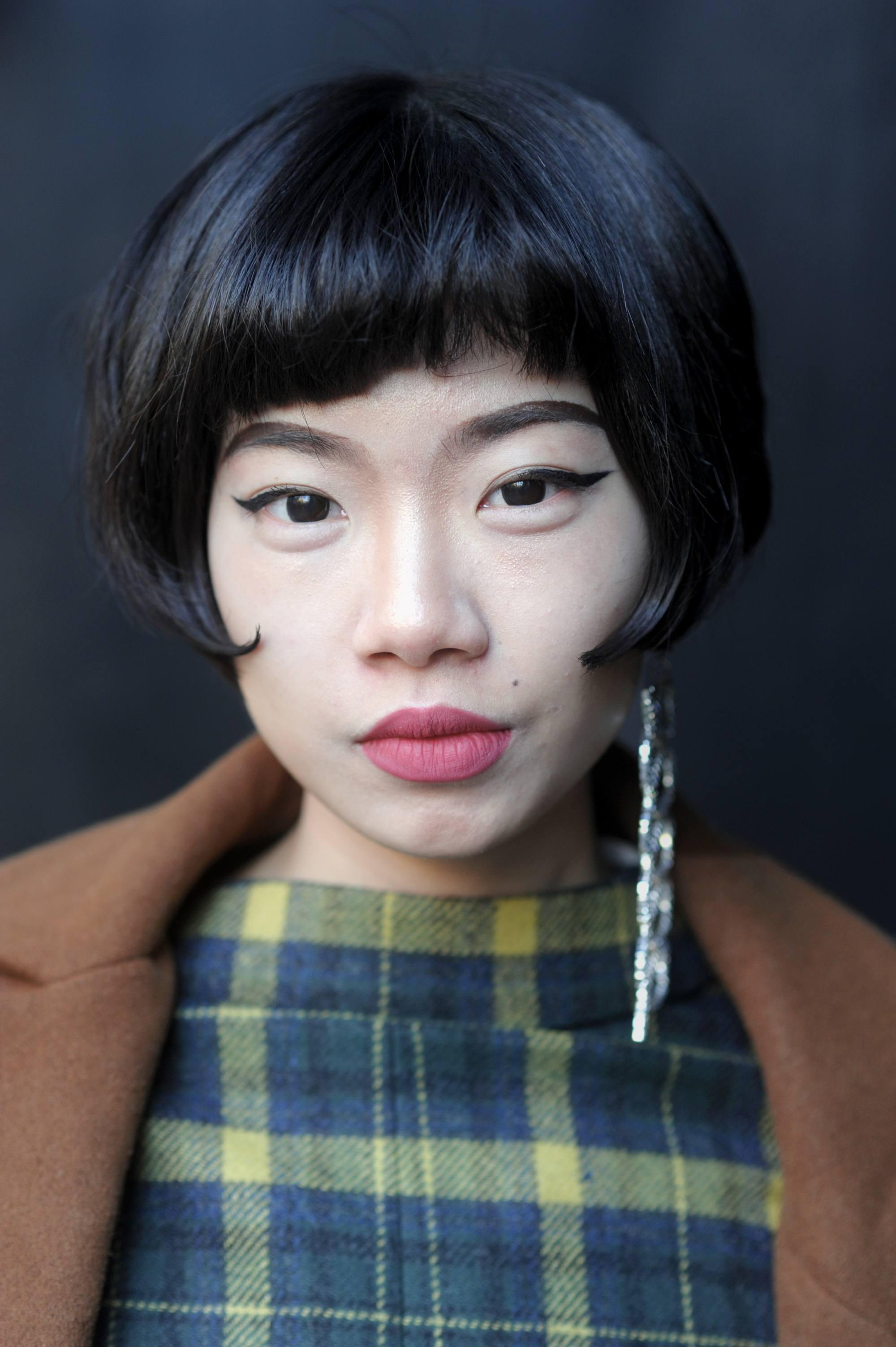 chanel haircut: close up shot of harper lin with short bob hairstyle and sleek blunt bob, wearing checked dress and statement earring