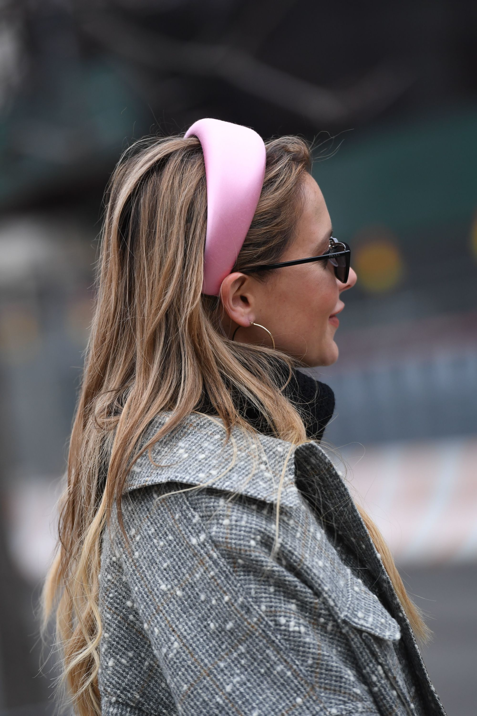 Hair trends 2019: Street style woman with long dirty blonde hair wearing a satin pink headbands and sunglasses.