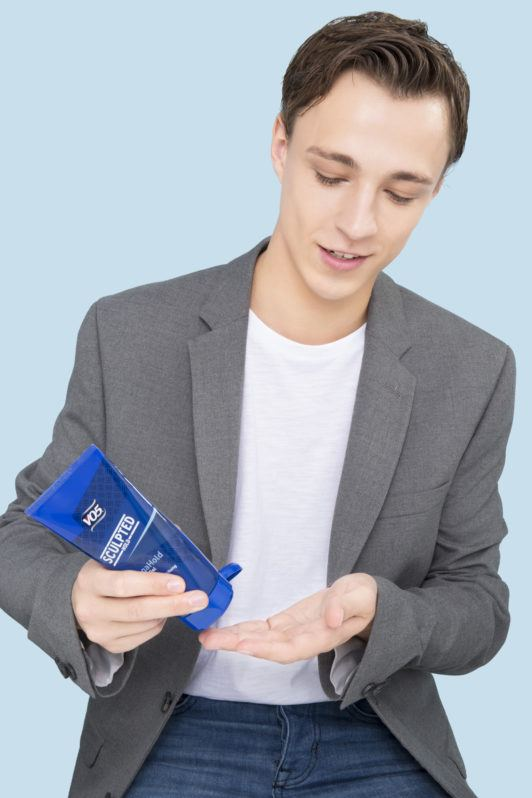How to use hair gel man squeezing gel into hand looking down