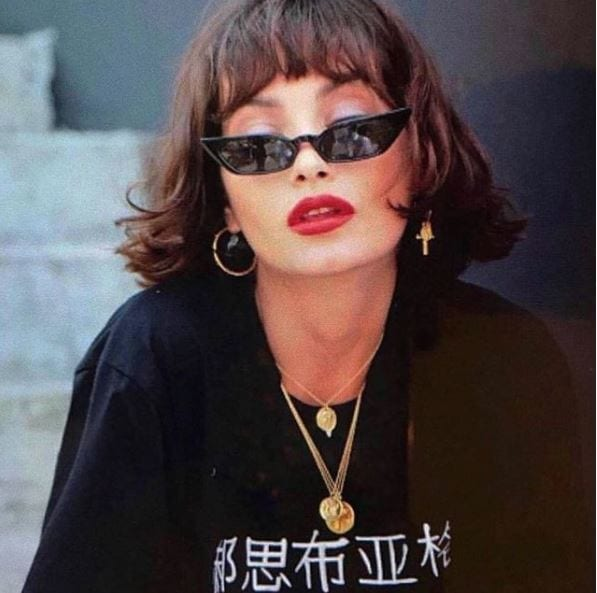 woman with brown hair bob and bangs with micro sunglasses